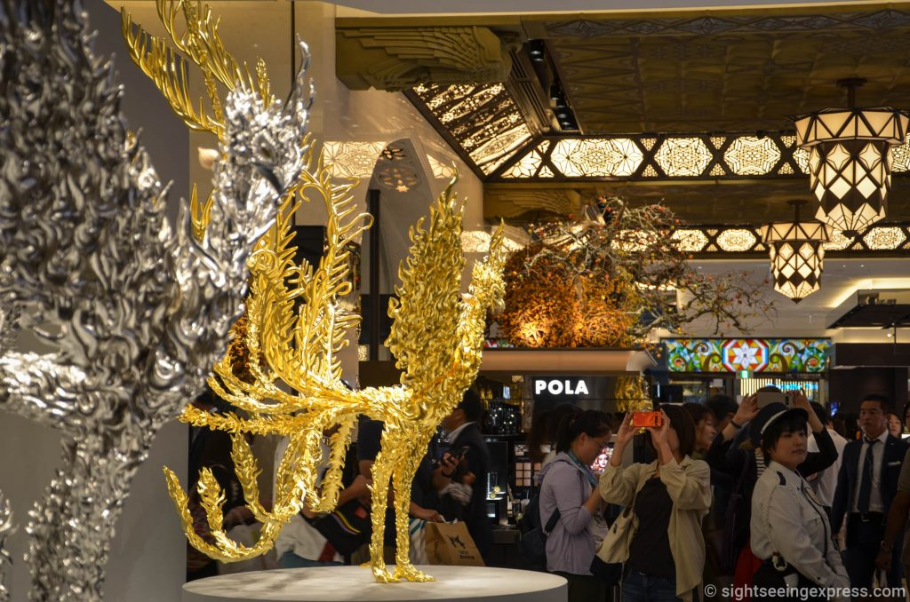Two golden and platinum phoenix statues at Daimaru shopping center