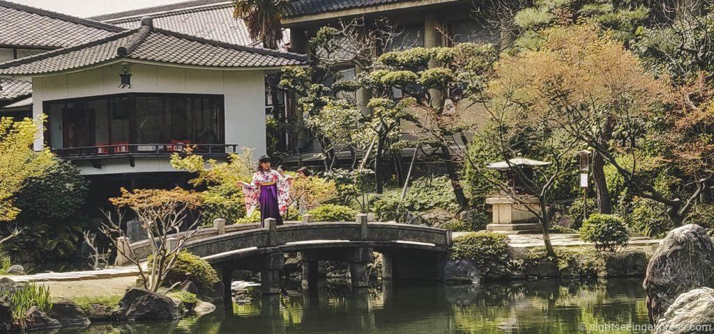 Kimono girl on a bridge in a Japanese garden